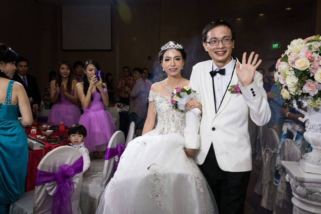 The groom waving to guests at a Singapore Chinese wedding dinner.