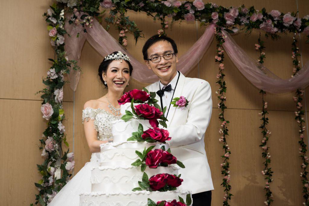 Cutting the cake, wedding photography service by Shilton Tan.