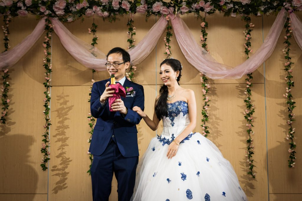 Popping the champagne, photo by Singapore wedding photographer Shilton Tan.