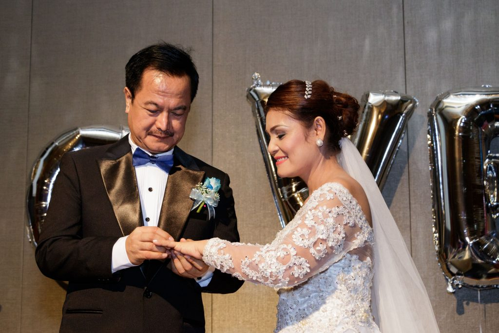 Exchanging rings at a wedding anniversary at Sheraton Towers.