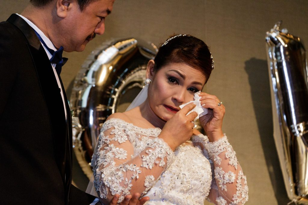The bride wiping her tears.