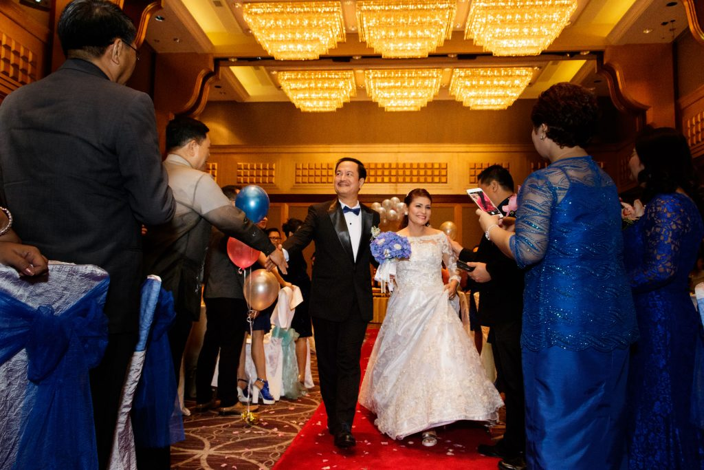 A couple marching into the ballroom at a wedding anniversary at Sheraton Towers.