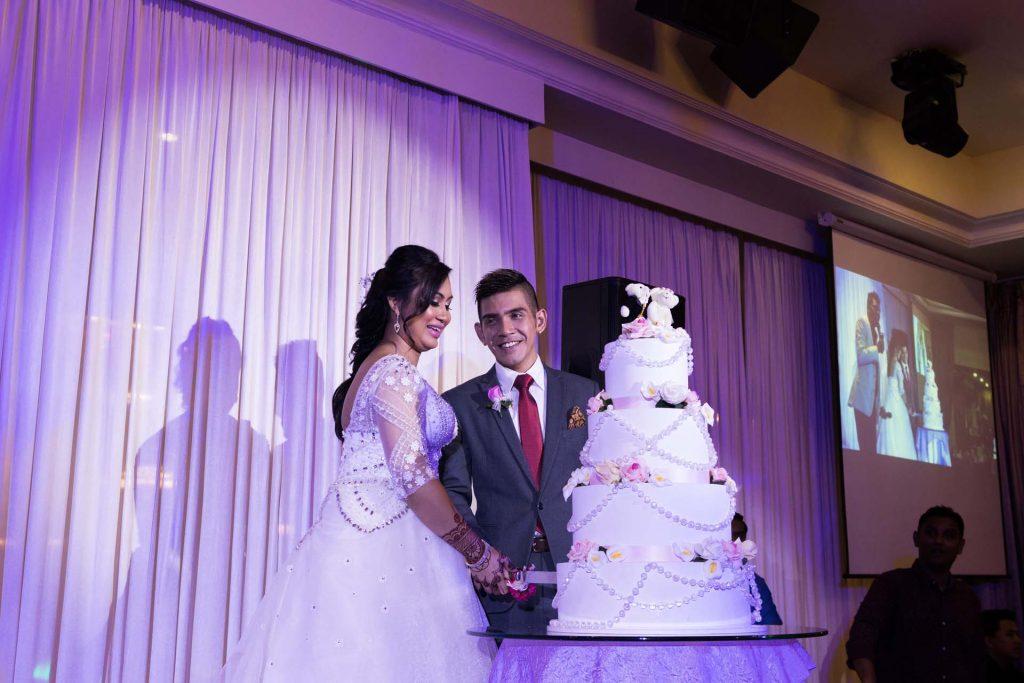 Cutting the wedding cake, photo by Singapore wedding photographer Shilton Tan.