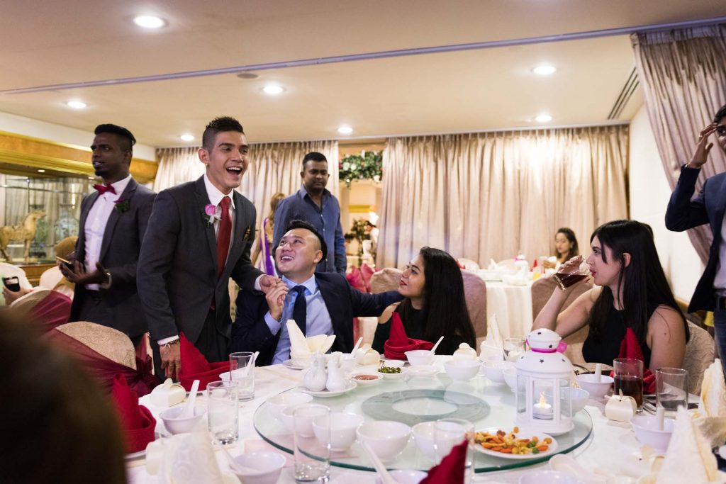 The groom meeting the guests at a weddings, photo by Singapore wedding photographer Shilton Tan.