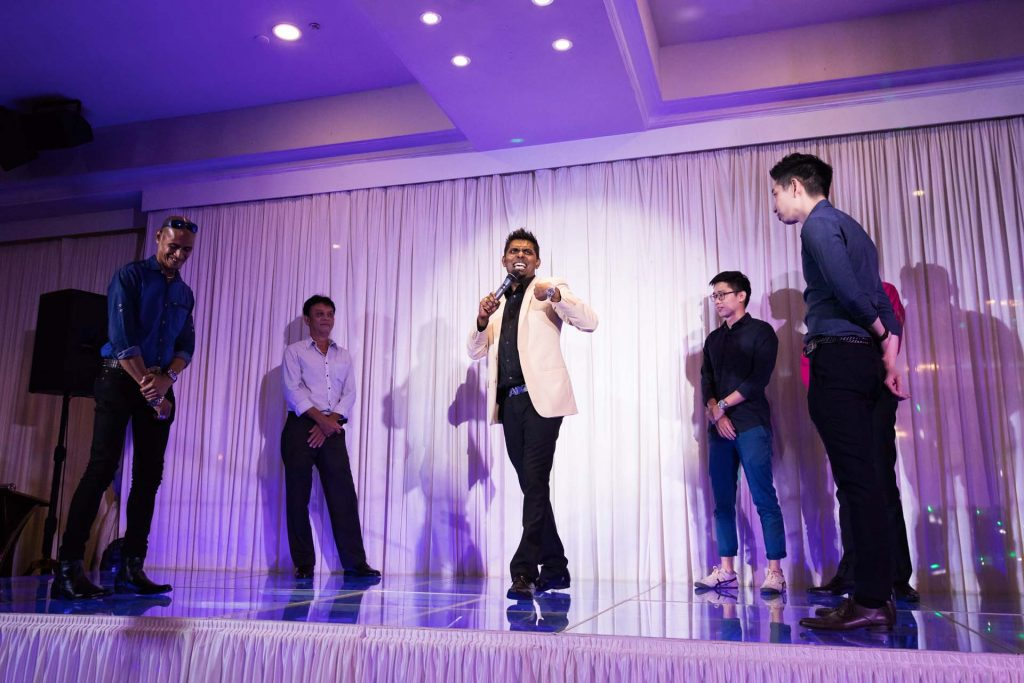 The emcee hosting a game at a wedding, wedding photography by Singapore photographer Shilton Tan.