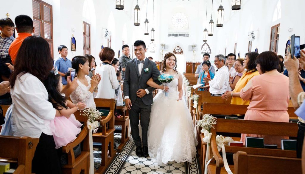 The couple entering the Church of Saints Peter and Paul, Singapore at their wedding.