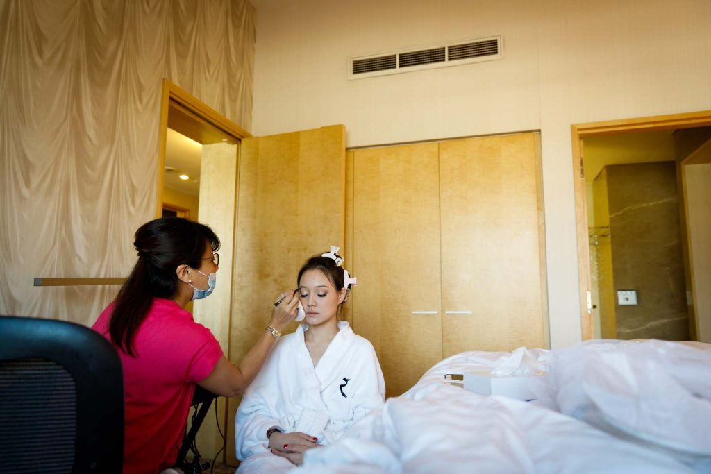 The bride getting her makeup done at Rendezvous Hotel Singapore.