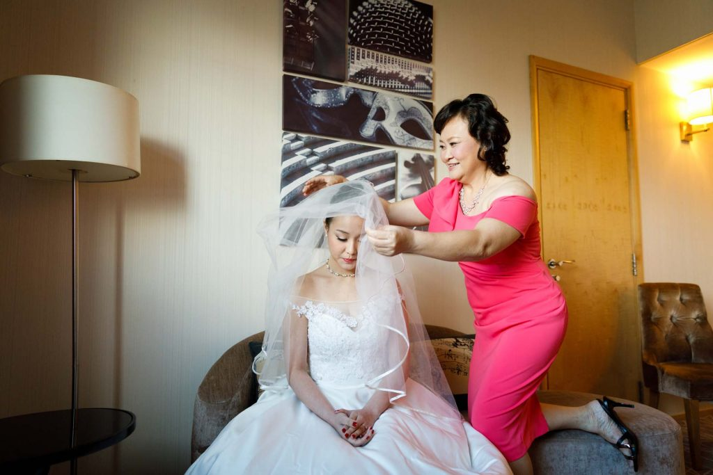Veiling the bride at a wedding at Rendezvous Hotel Singapore.